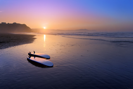 Sopelana beach with surfboards on the shore at sunset