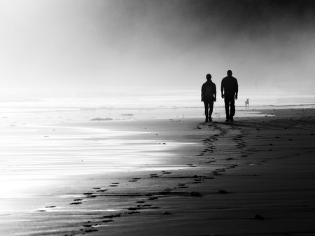 two: couple walking on beach. Black and white