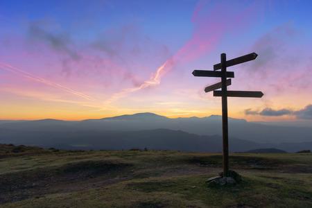 wooden signpost on mountain at sunset