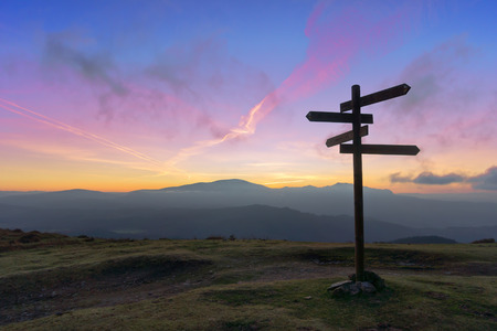 wooden signpost on mountain at sunset