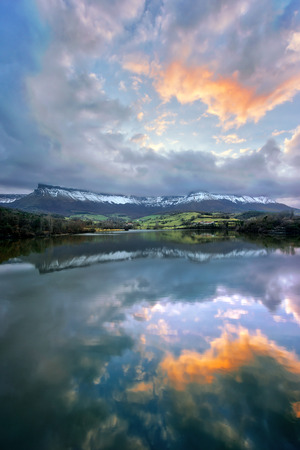 alava: Lake reflection at sunset with Sierra Salvada mountains Stock Photo
