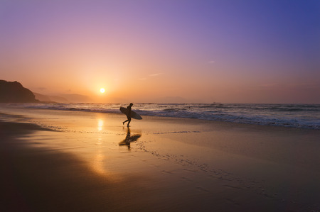 surf: surfer entering water at the sunset