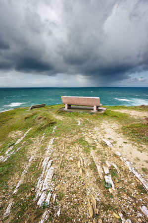 downpour: benches near sea with stormy clouds and downpour