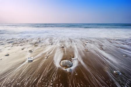 seascape with wave foam over the rocks Standard-Bild
