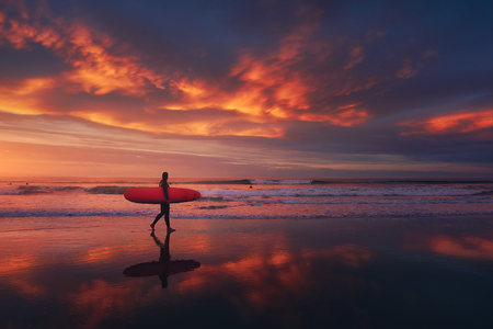 surfer in the beach at sunset with a red sky