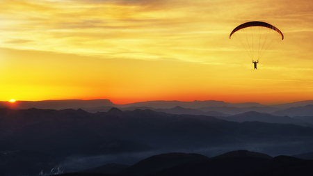 Paraglide silhouette over mountains at the sunset