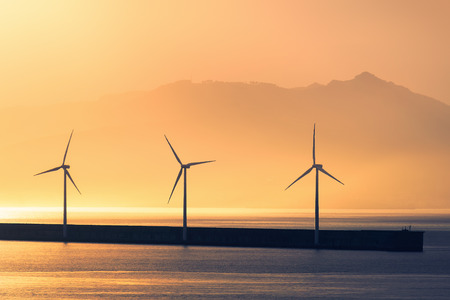sea wind turbines at sunset Archivio Fotografico