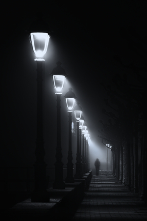 person walking on dark street illuminated with streetlamps. Black and white