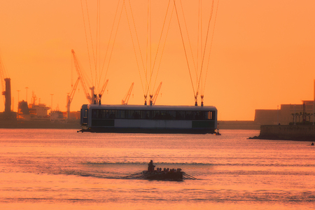 Hanging bridge and oarsmen at the sunset