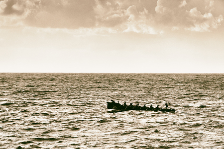 Oarsmen rowing on sea on trainera with vintage filter effect