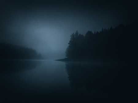 dark moody landscape of a lake and forest