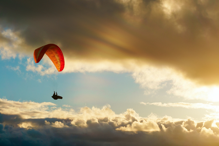 paraglider paragliding over the clouds at sunset Banque d'images