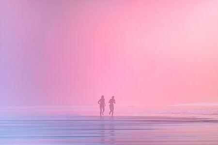people running on beach at sunset
