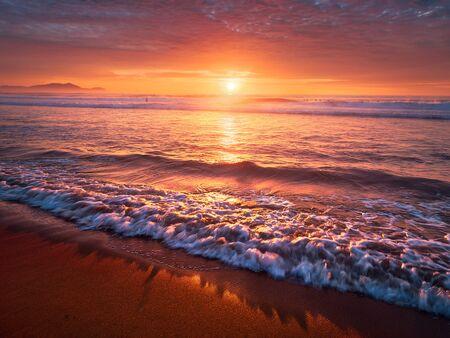 해안에 파도와 함께 해변의 아름다운 붉은 석양 스톡 콘텐츠