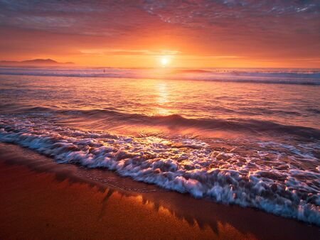 beautiful red sunset on beach with a wave on the shore Banco de Imagens