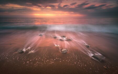 long exposure seascape with rocks and waves on beach 版權商用圖片