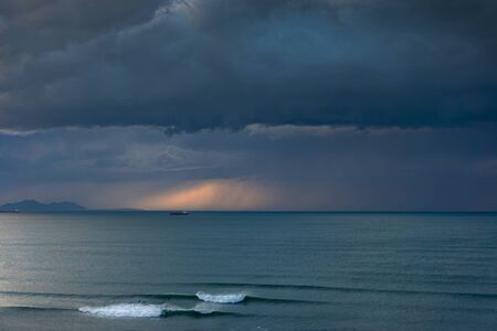 dark seascape with stormy clouds and some waves
