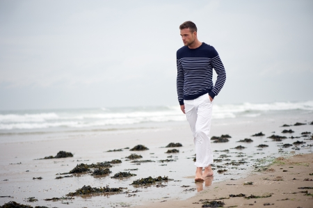 western europe: A young man walking on the beach in Western Europe