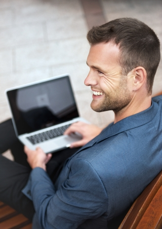 A young man sitting in the city and smiling with a laptop photo