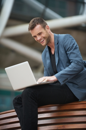 A young man sitting in the city with a laptop photo