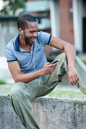 telephone headsets: Un hombre negro joven escuchando m�sica en los auriculares Foto de archivo