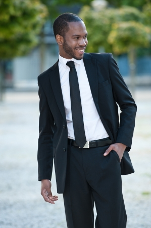 A handsome man smiling in a suit outside photo