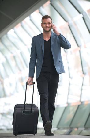 suitcases: Een jonge man Walking in de stad door het metrostation met een mobiele telefoon en koffer in de hand
