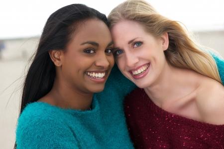 Multiculturele vrienden lachen, glimlachen en knuffelen buitenshuis.