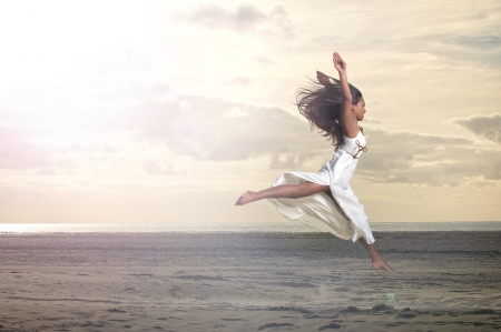 An african girl jumping in a white dress at the beach