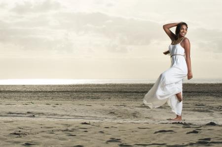 danza africana: Una ragazza africana che fa un ballo posa con un sorriso in spiaggia