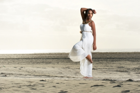 Beautiful african american girl  in a white dress doing a dance pose at the beach