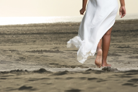 An African American girl is walking on the beach.  photo