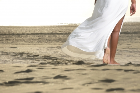 An African American girl is walking on the beach with a flowing white dress.