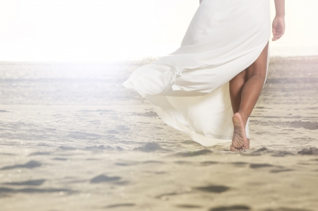An African American girl is walking on the sand with a flowing white dress.