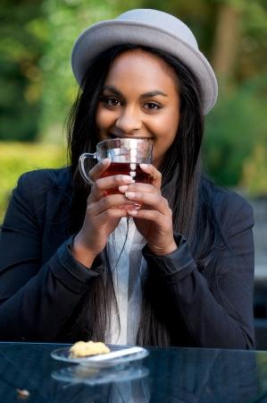 Belle Fille Souriant Noir et boire du thé dans un café extérieur Banque d'images