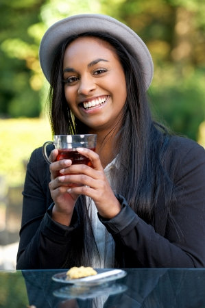 Smiling African Girl Drinking Tea Outdoors photo