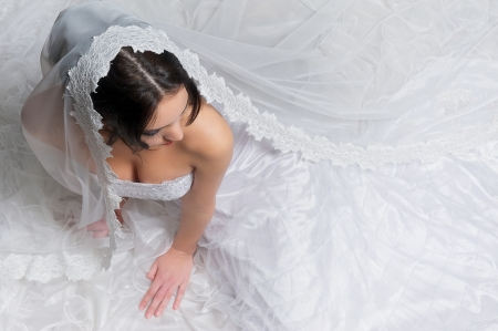 Looking down on a model sitting on the floor with a long white wedding dress  photo