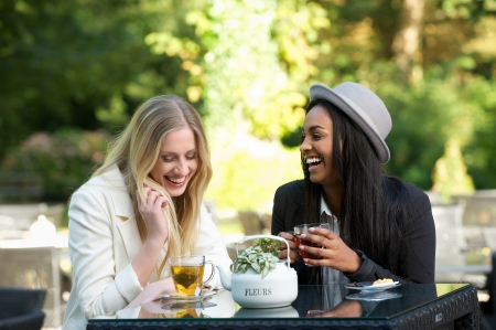 two girls drinking tea and laughing outdoors