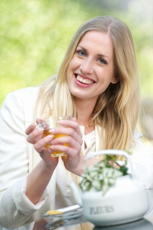 woman drinking tea: A young blonde girl is holding a cup of tea outdoors
