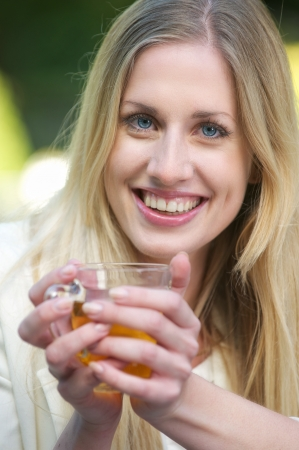 A young blonde girl is smiling and holding a cup of tea outdoors  photo