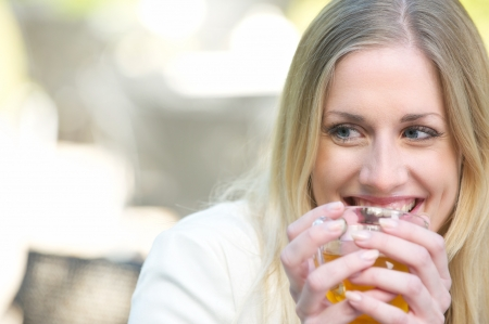A young blonde girl is drinking a cup of tea outdoors  photo