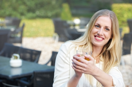 A blonde girl is looking away and smiling with a cup of tea in her hand photo