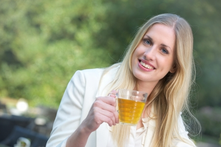 Blonde girl holding up a cup of tea photo