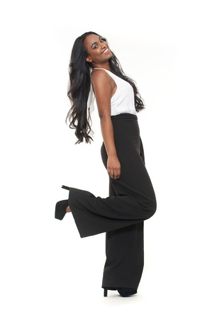 happy african woman: Young smiling mixed race girl is wearing black trousers and white shirt isolated against white back ground in the studio. She is lifting her leg in a dance pose.