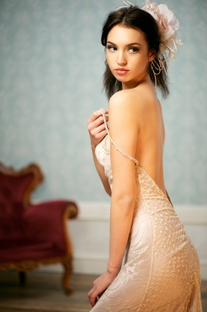 A portrait of a beautiful young bride holding up her shoulder strap and looking over her shoulder photo