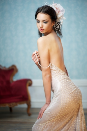 A seductive pose of a young bride fixing her dress Stock Photo
