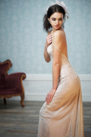 A young girl in a white wedding dress is glancing over her shoulder Stock Photo