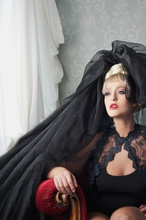 Beautiful blond european fashion girl with black couture head dress, sitting on a chair and looking out the window photo