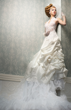 Very tall caucasian bride is posing in a dream like white wedding dress and posing against the wall Stock Photo