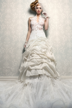 Tall, sexy and alluring caucasian bride in long luxurious wedding dress photo